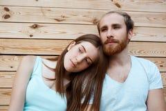 Junges schönes Paarlächeln, werfend über Hintergrund der hölzernen Bretter auf Lizenzfreie Stockbilder