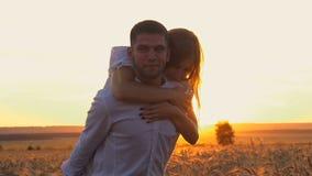Junges schönes Paarmädchen und -junge, die auf einem Weizengebiet bei Sonnenuntergang spielt und flirtet Der Kerl hält das Mädche stock video footage