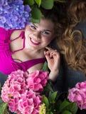 Junges schönes plus das vorbildliche Lügen der Größe in den Blumen, xxl Frau Stockfoto