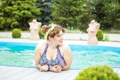 Junges schönes plus das vorbildliche Spritzen der Größe im Pool Lizenzfreies Stockfoto