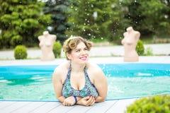 Junges schönes plus das vorbildliche Spritzen der Größe im Pool Lizenzfreie Stockfotos