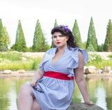 Junges schönes plus Größenmodell im Kleid nahe dem See Stockfoto