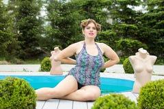 Junges schönes plus vorbildliches Sitzen der Größe durch das Pool draußen Stockfoto