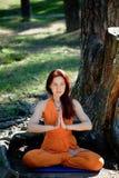 Junges schönes rothaariges Mädchen tut Yoga im Park auf grünem Hintergrund Lizenzfreies Stockbild