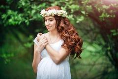 Junges schönes schwangeres Mädchen mit dem langen braunen Haar im weißen Kleid mit Blumenkranz auf ihrem Kopf Stockfotografie