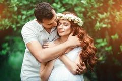 Junges schönes schwangeres Mädchen mit ihrem Ehemann mit Spielzeugbären im grünen Garten Lizenzfreies Stockfoto