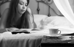 Junges schönes sexy Frauenlesebuch auf einem Bett im Hotelzimmer Rebecca 6 Stockfotografie