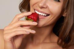 Junges schönes sexy Mädchen mit dem dunklen gelockten Haar, den bloßen Schultern und dem Hals, Erdbeere halten, um den Geschmack  Lizenzfreies Stockbild