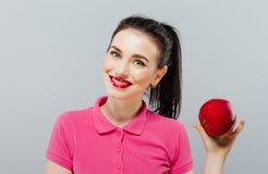 Junges schönes sexy Mädchen mit dem dunklen Haar, großen roten Apfel halten, um den Geschmack zu genießen und nähren, gesunde Ern Lizenzfreies Stockbild