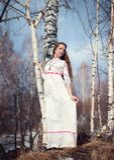 Junges schönes slawisches Mädchen mit dem langen Haar und slawischen ethnischen der Kleidung, die im Frühjahr Wald nahe Birke auf Lizenzfreies Stockbild