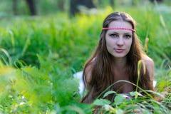 Junges schönes slawisches Mädchen mit dem langen Haar und slawischer ethnischer Kleidung liegt im Gras in einem Sommerwald Lizenzfreies Stockfoto