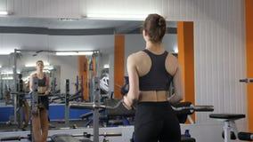 Junges schönes sportliches Mädchen anhebende Barbellstange in der Turnhalle, pumpendes Bizeps 60 fps stock video footage