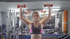 Junges schönes sportliches Mädchen, welches die Schulterpresse mit Dummköpfen trainierend in einer Sportturnhalle tut stock footage