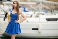Junges schönes städtisches Mädchen, das über Yachthafen aufwirft Lizenzfreie Stockfotos