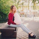 Junges schönes stilvolles Mädchen, das auf der Bank im Park mit Zuckerwatte sitzt Stockfotos