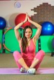 Junges schönes weißes Mädchen in einer rosa Sportklage meditiert auf der Yogaklasse in der Eignungsmitte lizenzfreie stockbilder