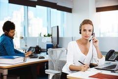 Junges schönes weibliches Stütztelefonbetreibersprechen, beraten, über Bürohintergrund lizenzfreies stockbild