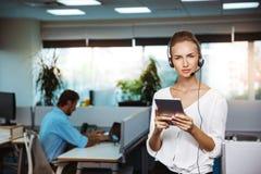 Junges schönes weibliches Stütztelefonbetreibersprechen, beraten, über Bürohintergrund lizenzfreies stockfoto