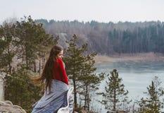 Junges sch?nes M?dchen, das auf einem Hintergrund von See aufwirft lizenzfreie stockfotografie