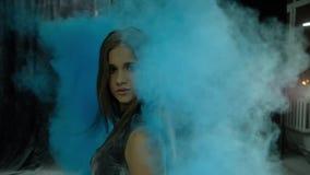 Junges sch?nes M?dchen in einer holi Farbenwolke auf einem dunklen Hintergrund, Zeitlupe stock footage