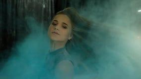 Junges sch?nes M?dchen in einer holi Farbenwolke auf einem dunklen Hintergrund, Zeitlupe stock video