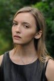 Junges schüchternes blondes braunäugiges Mädchen mit dem langen geraden Haar im blac Lizenzfreie Stockbilder