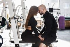Junges schlankes hübsches Mädchen und grober athletischer Mann sitzen zusammen auf leicht sich berühren der Sportbank ihrem lizenzfreie stockbilder