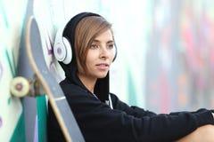 Junges Schlittschuhläufermädchen, das Musik mit Kopfhörern hört Stockfotografie