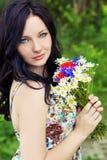 Junges schönes elegantes Mädchen, blaue Augen mit dem langen schwarzen Haar, das im Garten einen Blumenstrauß von Gänseblümchenmo Lizenzfreies Stockbild