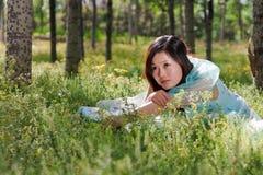 Junges schönes Mädchen, das auf das Blumenfeld legt Stockfoto