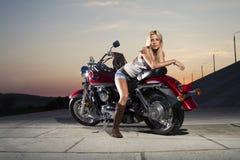 Junges schönes Mädchen mit einem Motorrad Stockbild