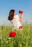 Junges schönes ruhiges Mädchen, das auf einem Mohnblumenfeld, Sommer im Freien träumt Lizenzfreies Stockfoto