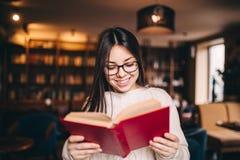 Junges schönes Studentenmädchen las Buch auf weißem Hintergrund Stockfotografie