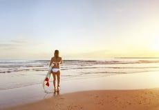 Junges schönes Surfermädchen, das in Richtung zur Brandung bei Sonnenaufgang geht Stockfotos