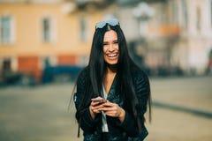 Junges schönes zufälliges Frauensimsen/um ihren Handy ersuchend Stockfotografie