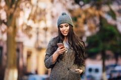 Junges schönes zufälliges Mädchen, das an ihrem Handy auf Frühlingsstadtstraße simst Stockfoto