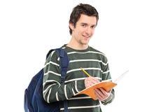 Junges Schreiben des männlichen Studenten in einem Notizbuch Stockbilder