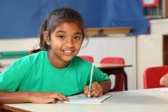 Junges Schulemädchen 9, das an ihrem Klassenzimmerschreibtisch schreibt Lizenzfreie Stockbilder