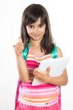 Junges Schulmädchen mit einer Tablette und einer Schultasche, die sich Daumen zeigen Stockbilder