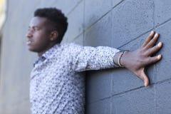 Junges schwarzer Mann tragendes Kenyanflaggenarmband mit dem Arm strecken aus Lizenzfreie Stockfotos
