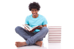 Junges schwarzes Jugendstudentenmannablesen Bücher - afrikanische Leute Stockfoto