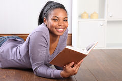 Junges schwarzes Kursteilnehmermädchen-Lesebuch zu Hause Lizenzfreie Stockfotografie