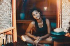Junges schwarzes Mädchen, das auf Veranda der kleinen Hütte sitzt Lizenzfreie Stockbilder