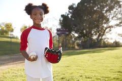 Junges schwarzes Mädchen, das Baseball halten und Handschuh, der zur Kamera schaut stockbild