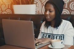 Junges schwarzes Mädchen im Café, das an Laptop arbeitet stockbilder