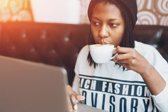 Junges schwarzes Mädchen in trinkendem Kaffee des Cafés und Arbeit über Laptop stockfoto