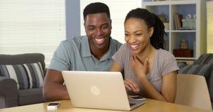 Junges schwarzes Paargraseninternet auf Laptop zusammen Lizenzfreies Stockfoto