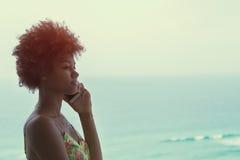 Junges schwarzes schönes Mädchen mit dem gelockten Haar, das am Telefon spricht lizenzfreie stockfotografie