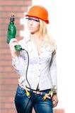 Junges sexi herrische blonde Dame im Sturzhelm mit Bohrgerät Stockfotos