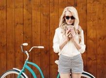 Junges sexy blondes Mädchen mit dem langen Haar in der Sonnenbrille, die nahes Weinlesegrünfahrrad steht und einen Tasse Kaffee h Stockbild
